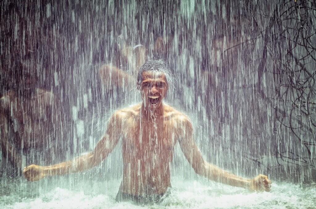 choosing the right lube for sex is can make it feel like you're playing in a waterfall like this man who is under a waterfall with a smile on his face